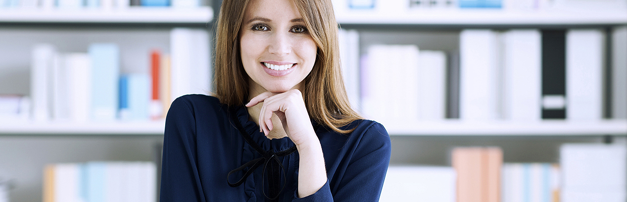 Confident beautiful businesswoman sitting at desk and posing, she is smiling at camera, office shelves on background